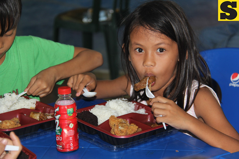 This child from a poor family in Cebu enjoys the food served during the Table of Hope Banquet in Cebu City, Philippines.