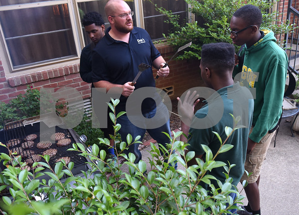 Volunteer Nathan Ledkins talks with John Tyler High School students Demonte Robinson, left, Emmanuel Daniels and Demetri Moore while he grills hamburgers during Young Life Wednesday night May 4, 2016 in Tyler. Young Life Tyler is an organization that seeks to share God's love with kids through the simple act of being present in their lives. Tyler Young Life is the longest consecutive running young life club in the world and has grown.    (Sarah A. Miller/Tyler Morning Telegraph)