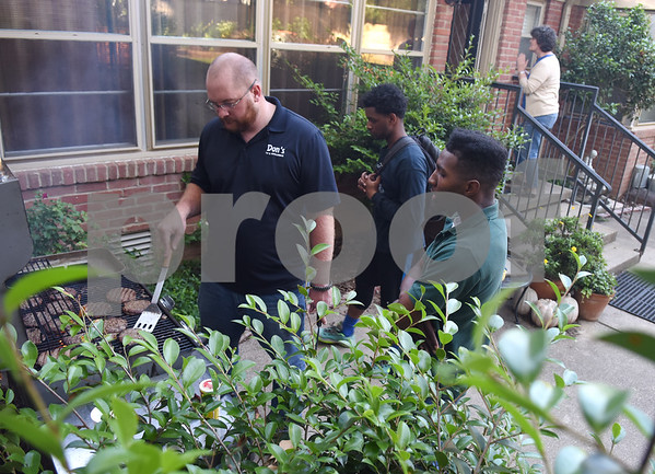 Volunteer Nathan Ledkins talks with John Tyler High School students Demonte Robinson and Emmanuel Daniels while he grills hamburgers during Young Life Wednesday night May 4, 2016 in Tyler. Young Life Tyler is an organization that seeks to share God's love with kids through the simple act of being present in their lives. Tyler Young Life is the longest consecutive running young life club in the world and has grown.    (Sarah A. Miller/Tyler Morning Telegraph)