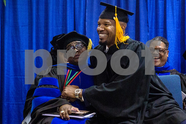 Provost and Vice President for Academic Affairs Glenell Lee-Pruitt makes a face and laughs as Jamie Foxx falls into the seat next to her during Jarvis Christian College's commencement at Jarvis Christian College in Hawkins, Texas, on Saturday, May 5, 2018. Jesse J. Holland, race and ethnicity writer for the Associated Press, gave the keynote address, and Foxx received an honorary doctorate degree from the college. (Chelsea Purgahn/Tyler Morning Telegraph)