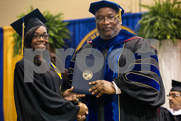 A graduate poses with president Lester Newman for a photo during Jarvis Christian College's commencement at Jarvis Christian College in Hawkins, Texas, on Saturday, May 5, 2018. Jesse J. Holland, race and ethnicity writer for the Associated Press, gave the keynote address, and Jamie Foxx received an honorary doctorate degree from the college. (Chelsea Purgahn/Tyler Morning Telegraph)