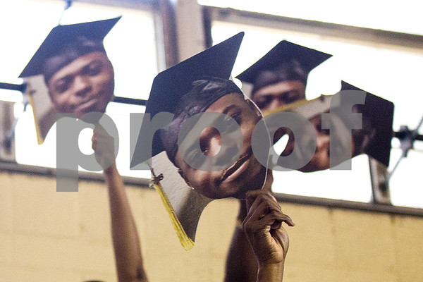 People hold signs of a graduate's face during Jarvis Christian College's commencement at Jarvis Christian College in Hawkins, Texas, on Saturday, May 5, 2018. Jesse J. Holland, race and ethnicity writer for the Associated Press, gave the keynote address, and Jamie Foxx received an honorary doctorate degree from the college. (Chelsea Purgahn/Tyler Morning Telegraph)