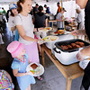 Record-Eagle/Keith King<br /> Sarah Parker, of Traverse City, is served a buffalo burger as her daughters Audrey Parker, 5, and Macy Parker, far left, 2, stand near Sunday, May 22, 2011 during the 56th annual Northwestern Michigan College Barbecue.