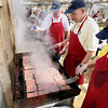 Record-Eagle/Keith King<br /> Volunteers Pete Strom, from right, and his son Michael Strom, both members of the Traverse City Rotary Club, prepare buffalo burgers Sunday, May 22, 2011 during the 56th annual Northwestern Michigan College Barbecue.