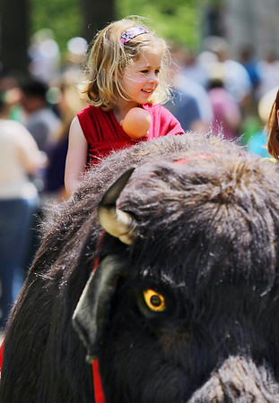"Record-Eagle/Keith King<br /> Kinsey Hintz, 4, of Traverse City, holds her doll as she sits atop ""Chip,"" an artificial buffalo, Sunday, May 22, 2011 during the 56th annual Northwestern Michigan College Barbecue."