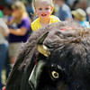 "Record-Eagle/Keith King<br /> Sophia Vincent, 2, of Traverse City, sits atop ""Chip,"" an artificial buffalo, Sunday, May 22, 2011 during the 56th annual Northwestern Michigan College Barbecue."