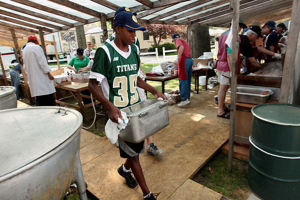 Record-Eagle/Keith King<br /> Marcus Hogue, a volunteer and Traverse City West High School football player, carries beans toward the area where food is served Sunday, May 20, 2012 prior to the start of the 57th annual Northwestern Michigan College Barbecue.