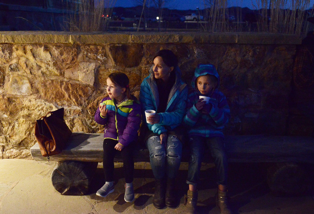 Justin Sheely | The Sheridan Press<br /> Guests, from left, Ever Poll, 4, Nichole Poll and Vella Poll, 8, sit outside to enjoy their treats during the 5th annual Ucross Christmas Celebration at the Raymond Plank Creative Center at Ucross Saturday, Dec. 9, 2017.