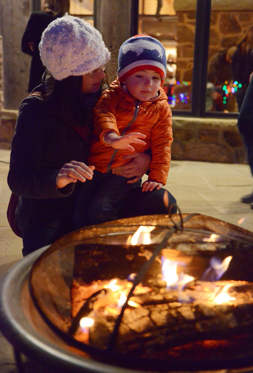 Justin Sheely | The Sheridan Press<br /> Jennifer Graslie and her son Caleb Graslie, 3, warm by the fire during the 5th annual Ucross Christmas Celebration at the Raymond Plank Creative Center at Ucross Saturday, Dec. 9, 2017.
