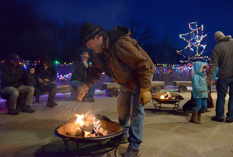 Justin Sheely | The Sheridan Press<br /> Ucross employee Marty Jelly puts a log on the fire during the 5th annual Ucross Christmas Celebration at the Raymond Plank Creative Center at Ucross Saturday, Dec. 9, 2017.