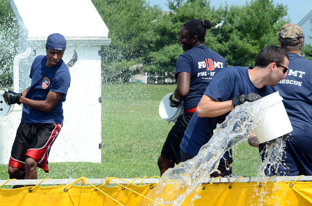. Fire Department of Motgomery Township Company members take part in a bucket brigade competition during the 14th annual Montgomery County Fifth Fire District Water Battle held at the Towamencin Firehouse on Saturday morning July 12,2014.Photo by Mark C Psoras/The Reporter