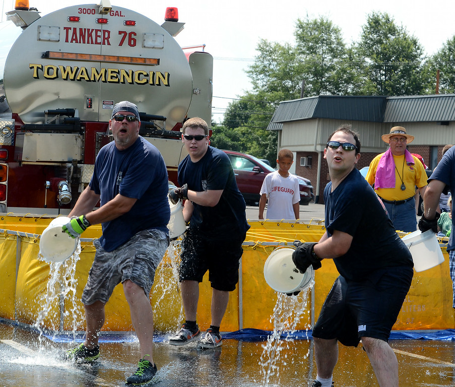 . North Penn  Fire Company members take part in a bucket brigade competition during the 14th annual Montgomery County Fifth Fire District Water Battle held at the Towamencin Firehouse on Saturday morning July 12,2014.Photo by Mark C Psoras/The Reporter