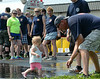 North Penn Fire Company member Stephen Forbes splashes in a puddle with Payton Burkart ,16 mos, during the 14th annual Montgomery County Fifth Fire District Water Battle held at the Towamencin Firehouse on Saturday morning July 12,2014.Photo by Mark C Psoras/The Reporter