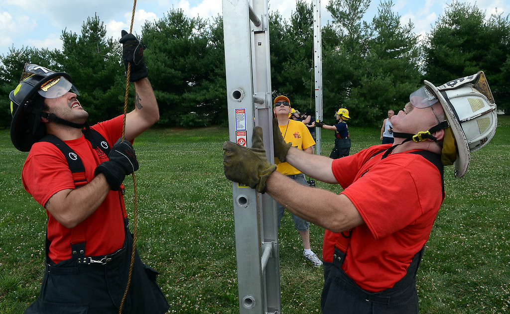 . Towamencin Fire Company members raise a ladder as they compete in the 14th annual Montgomery County Fifth Fire District Water Battle held at the Towamencin Firehouse on Saturday morning July 12,2014.Photo by Mark C Psoras/The Reporter