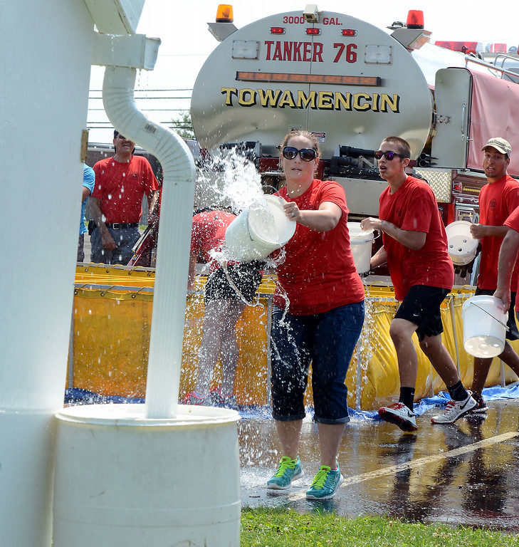 . Towamencin Fire Company members take part in a bucket brigade competition during the 14th annual Montgomery County Fifth Fire District Water Battle held at the Towamencin Firehouse on Saturday morning July 12,2014.Photo by Mark C Psoras/The Reporter