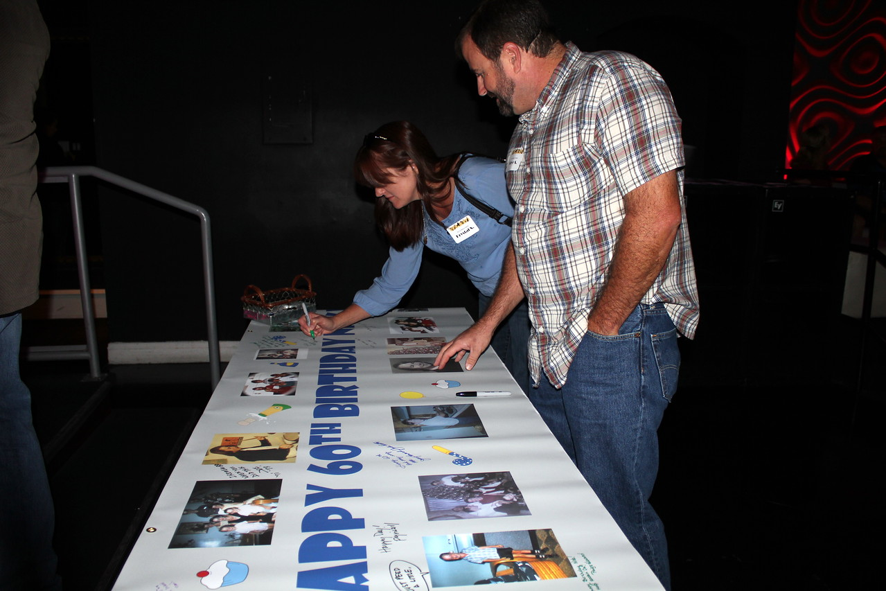 Steve and Krystal Sawyer sign the banner.