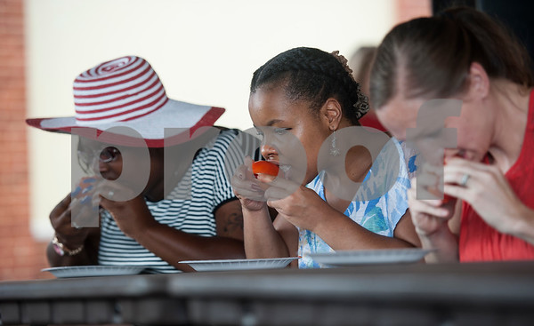 LaTonya Ross of Tyler, left, and Ashley Lemle of Longview, center, compete in a tomato peeling contest during the Jacksonville Tomato Fest Saturday June 11, 2016 in Jacksonville, Texas. In its 32nd year, the week-long festival included tomato themed events such as a salsa contest,  best homegrown tomato contest and eating contest as well as other activities such as a murder mystery dinner, ski show and dodgeball tournament.  (Sarah A. Miller/Tyler Morning Telegraph)