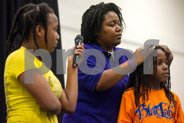 RaQuelle Whitman, 10, holds the microphone as her mother Kalae puts dry shampoo in her son Judah's, 7, hair during a presentation at the East Texas Hair and Beauty Expo Hair at Harvey Hall Convention Center in Tyler, Texas, on Monday, June 12, 2017. The expo featured vendors and products from across the South. (Chelsea Purgahn/Tyler Morning Telegraph)