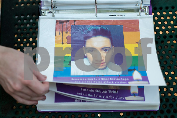 A person looks through a binder with pictures and information of victims of the Orlando Pulse nightclub shooting during a memorial in Tyler, Texas, on Monday, June 12, 2017. Monday marked the one year anniversary of the deadliest mass shooting in modern U.S. history. (Chelsea Purgahn/Tyler Morning Telegraph)
