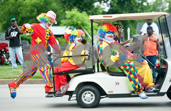 photo by Sarah A. Miller/Tyler Morning Telegraph  A clown jumps onto the back of a golf cart heading down Martin Luther King, Jr. Blvd. in Tyler, Texas Saturday morning June 14, 2014 during the annual Juneteenth Parade. The Juneteenth Parade and following celebration at Woldert Park commemorates the end the end of African slavery in the United States. Juneteenth is celebrated in cities throughout the South as well and has spread to other parts of the country. Tyler's parade and celebration included community leaders, motorcycle clubs, car clubs, sports teams and church groups. Free food at the park was provided by Brookshire's Grocery Company, and Brookshire's Senior Vice-President Division Manger Trent Brookshire was the parade Grand Marshal. Thousands of people lined the streets to watch the parade.