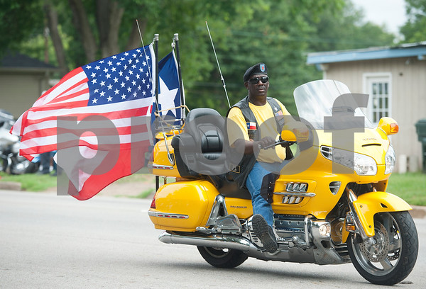 photo by Sarah A. Miller/Tyler Morning Telegraph  A man drives a motorcycle adorned with the American flag and Texas state flag in Tyler, Texas Saturday morning June 14, 2014 during the annual Juneteenth Parade. The Juneteenth Parade and following celebration at Woldert Park commemorates the end the end of African slavery in the United States. Juneteenth is celebrated in cities throughout the South as well and has spread to other parts of the country. Tyler's parade and celebration included community leaders, motorcycle clubs, car clubs, sports teams and church groups. Free food at the park was provided by Brookshire's Grocery Company, and Brookshire's Senior Vice-President Division Manger Trent Brookshire was the parade Grand Marshal. Thousands of people lined the streets to watch the parade.