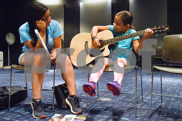 Jessi Tena holds music for Ally Rodriguez, 8, as she smiles while learning to play a song during free guitar lessons at the Tyler Public Library in Tyler, Texas, on Thursday, June 14, 2018. The library partnered with Guitar Center for their 2018 Summer Reading Program to host five beginner guitar lessons throughout the summer. (Chelsea Purgahn/Tyler Morning Telegraph)