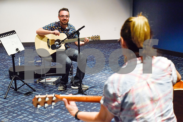 Brandon McManus leads free guitar lessons as Julie Lauer listens at the Tyler Public Library in Tyler, Texas, on Thursday, June 14, 2018. The library partnered with Guitar Center for their 2018 Summer Reading Program to host five beginner guitar lessons throughout the summer. (Chelsea Purgahn/Tyler Morning Telegraph)