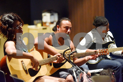 Stephanie Garcia, Josh Garcia and Rebekah Brookins tune their guitars during free guitar lessons at the Tyler Public Library in Tyler, Texas, on Thursday, June 14, 2018. The library partnered with Guitar Center for their 2018 Summer Reading Program to host five beginner guitar lessons throughout the summer. (Chelsea Purgahn/Tyler Morning Telegraph)