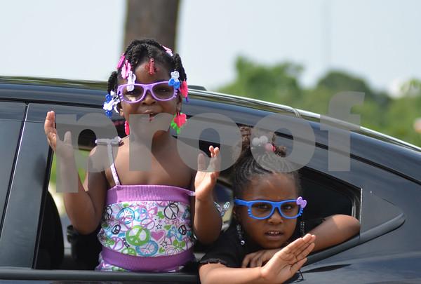 Girls greet parade atendees through a car window. (Victor Texcucano)