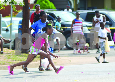 Children scramble to pick up candy thrown by parade cars on Saturday morning during the annual Juneteenth Parade on Martin Luther King Jr. Boulevard. (Victor Texcucano)