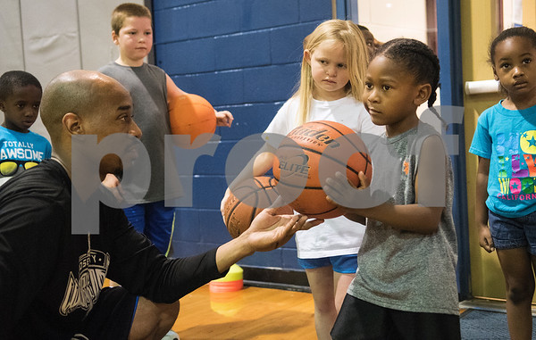 Coach Romen Tucker helps Teyano Davis, 5, with his form at his Rose City Warriors summer basketball camp at the Glass Recreation Center Monday June 19, 2017.  (Sarah A. Miller/Tyler Morning Telegraph)