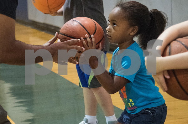 Coach Romen Tucker helps Reign McClendon, 5, with her form at his Rose City Warriors summer basketball camp at the Glass Recreation Center Monday June 19, 2017.  (Sarah A. Miller/Tyler Morning Telegraph)