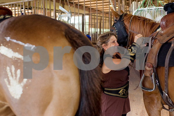 Cathy Merck smiles as she prepares her horse for competition during the quadrille competition at Super Ride XV at Henderson County Regional Fair Park Complex in Athens, Texas, on Wednesday, June 21, 2017. The event features a variety of equestrian competitions such as trick riding and vaulting. (Chelsea Purgahn/Tyler Morning Telegraph)