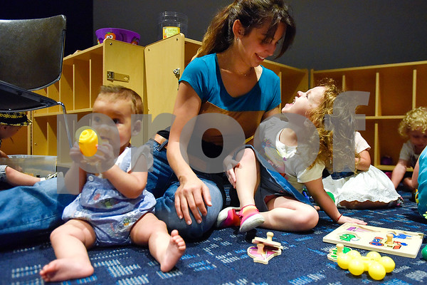 Aubree Jackson, 3, right, looks up and smiles at Yasmin Gad, center, while Hana Ismael, 7 months, plays with a sippy cup during a toddlers explore class at the Tyler Public Library in Tyler, Texas, on Wednesday, June 21, 2017. The weekly event includes a story time followed by play time with a variety of toys. (Chelsea Purgahn/Tyler Morning Telegraph)