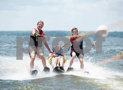 Volunteers George Ward, left, and Brendyn Cosby, right, assist Collin Mullins, 6, of Palestine and his speech therapist Susan Priest as they sit ski during the Lake Palestine Adaptive Aquafest Saturday June 25, 2016 in Bullard, Texas.  (Sarah A. Miller/Tyler Morning Telegraph)