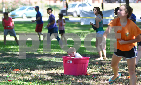 Reagan Cassity, 3, takes shelter from the heat of battle inside a tub of water balloons.(Victor Texcucano)