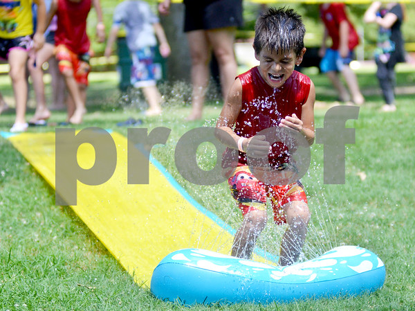 Juan Ordorica, 6, beats the Sunday afternoon heat by making his way down a slip 'n' slide. (Victor Texcucano)