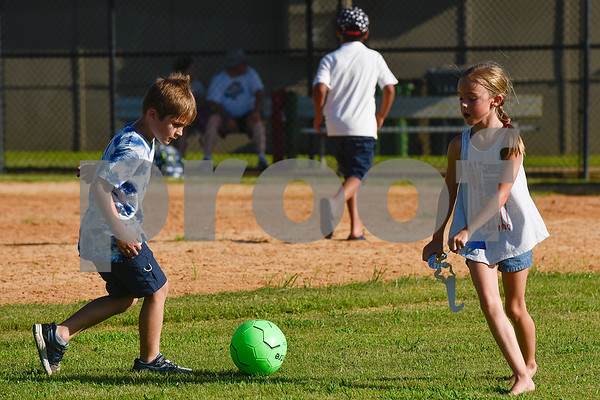 Jace Williams, 7, kicks a soccer ball around as other children run by during the family fireworks celebration at South Spring Baptist Church in Tyler, Texas, on Friday, June 30, 2017. The event featured live music, food trucks, bounce houses and fireworks for families to enjoy. (Chelsea Purgahn/Tyler Morning Telegraph)
