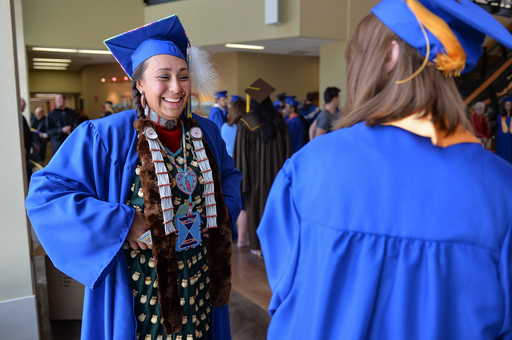 Justin Sheely | The Sheridan Press<br /> Coty Real Bird wears a Crow traditional elk-tooth dress as she visits with her fellow Criminal Justice graduates prior to the 68th Commencement Ceremony Saturday at Sheridan College.
