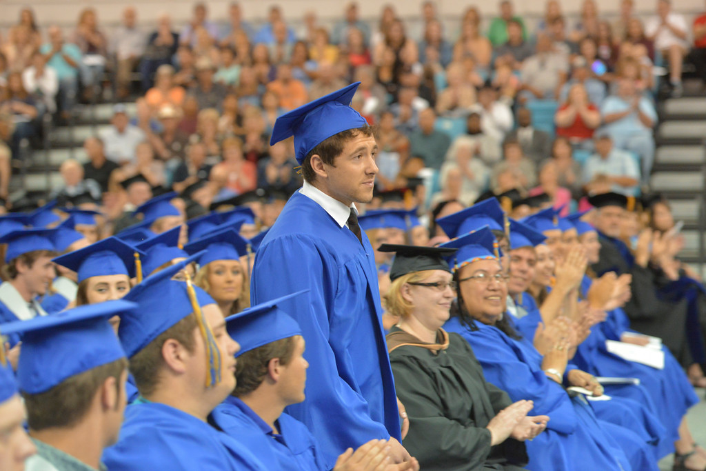 Justin Sheely | The Sheridan Press<br /> Graduate Dan Miller walks up to the stage after district president Paul Young announced him as the recipient of the President's Award during the 68th Commencement Ceremony Saturday in the Bruce Hoffman Golden Dome at Sheridan College.