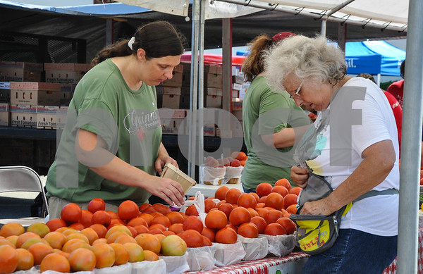 Jacksonville native Candace Reneau buys fresh homegrown tomatoes at the 34th Annual Tomato Fest on Saturday, June 9. The festival is held in Jacksonville every summer and includes many tomato contests. (Jessica T. Payne/Tyler Paper)