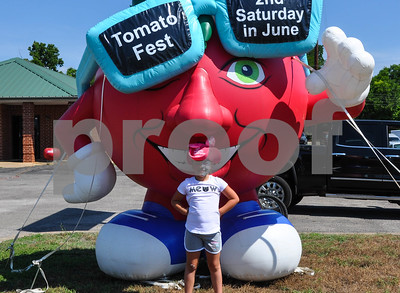 McKenna Adams, 7, of Mabank is all smiles while taking a photo with a large inflatable tomato at the 34th Annual Tomato Fest in Jacksonville. The festival is held the second Saturday in June and celebrates the city's famous tomatoes. (Jessica T. Payne/Tyler Paper)