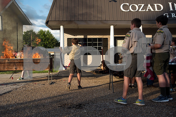Scouts participate in a flag retirement ceremony at Cozad Insurance Group in Lindale, Texas, on Tuesday, July 11, 2017. Scouts and members of the community retired 90 flags in the ceremony. (Chelsea Purgahn/Tyler Morning Telegraph)