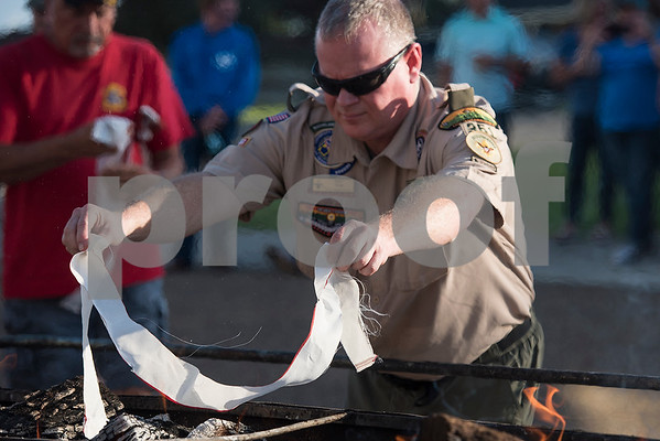 Ray New drops a stripe of a flag into the fire during a flag retirement ceremony at Cozad Insurance Group in Lindale, Texas, on Tuesday, July 11, 2017. Scouts and members of the community retired 90 flags in the ceremony. (Chelsea Purgahn/Tyler Morning Telegraph)