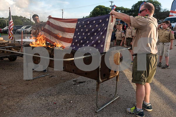 Kole Westberry, 18, and Ray New place the last American flag into the fire during a flag retirement ceremony at Cozad Insurance Group in Lindale, Texas, on Tuesday, July 11, 2017. Scouts and members of the community retired 90 flags in the ceremony. (Chelsea Purgahn/Tyler Morning Telegraph)