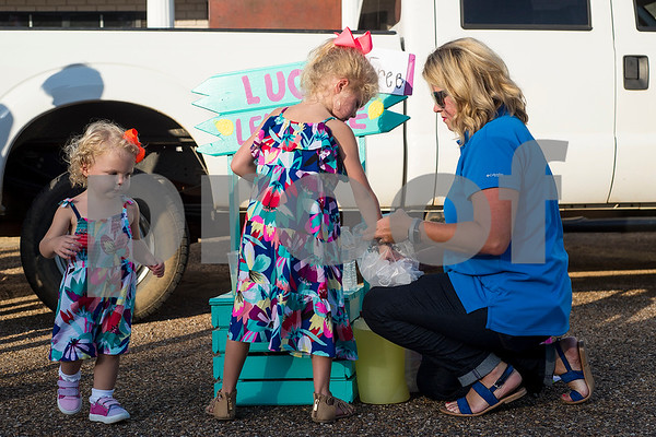 Rose, 20 months, Lucy, 6, and Claire Cozad prep a lemonade stand during a flag retirement ceremony at Cozad Insurance Group in Lindale, Texas, on Tuesday, July 11, 2017. Scouts and members of the community retired 90 flags in the ceremony. (Chelsea Purgahn/Tyler Morning Telegraph)