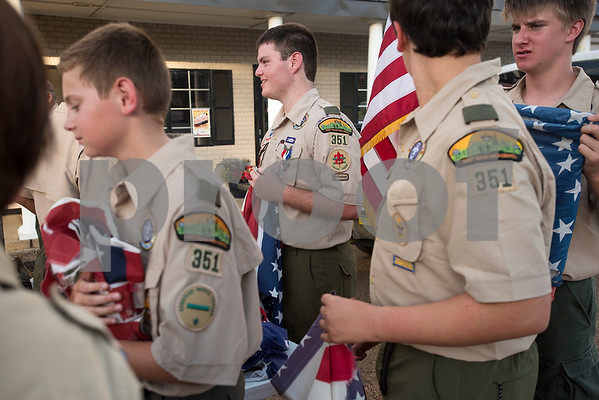 Cody New, 16, center, stand with other Scouts during a flag retirement ceremony at Cozad Insurance Group in Lindale, Texas, on Tuesday, July 11, 2017. Scouts and members of the community retired 90 flags in the ceremony. (Chelsea Purgahn/Tyler Morning Telegraph)