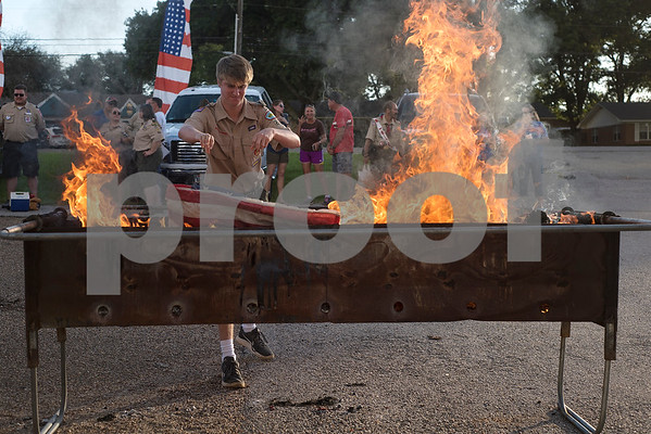 Jacob Rogers, 14, throws a flag into the fire during a flag retirement ceremony at Cozad Insurance Group in Lindale, Texas, on Tuesday, July 11, 2017. Scouts and members of the community retired 90 flags in the ceremony. (Chelsea Purgahn/Tyler Morning Telegraph)