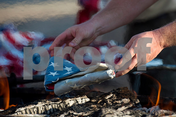 A person drops a flag into the fire during a flag retirement ceremony at Cozad Insurance Group in Lindale, Texas, on Tuesday, July 11, 2017. Scouts and members of the community retired 90 flags in the ceremony. (Chelsea Purgahn/Tyler Morning Telegraph)