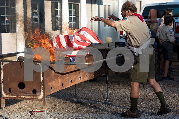 Tom Goodwin throws a flag into the fire during a flag retirement ceremony at Cozad Insurance Group in Lindale, Texas, on Tuesday, July 11, 2017. Scouts and members of the community retired 90 flags in the ceremony. (Chelsea Purgahn/Tyler Morning Telegraph)